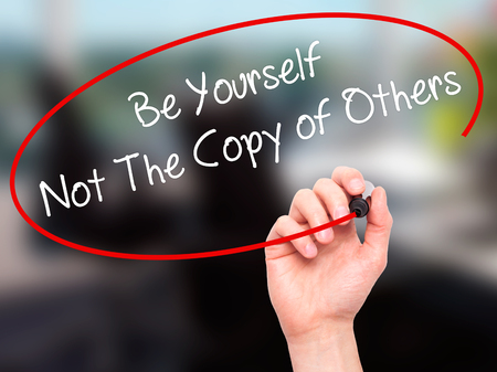 differentiation: Man Hand writing Be Yourself Not The Copy of Others with black marker on visual screen. Isolated on office. Business, technology, internet concept. Stock Photo