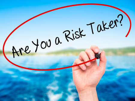 taker: Man Hand writing Are You a Risk Taker? with black marker on visual screen. Isolated on nature. Business, technology, internet concept. Stock Photo