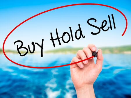 press agent: Man Hand writing  Buy Hold Sell with black marker on visual screen. Isolated on nature. Business, technology, internet concept. Stock Photo Stock Photo