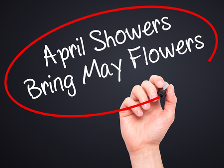 april: Man Hand writing April Showers Bring May Flowers with black marker on visual screen. Isolated on black. Business, technology, internet concept. Stock Photo