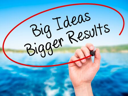 bigger: Man Hand writing Big Ideas Bigger Results  with black marker on visual screen. Isolated on nature. Business, technology, internet concept. Stock Photo