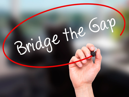 bridging the gap: Man Hand writing Bridge the Gap with black marker on visual screen. Isolated on office. Business, technology, internet concept. Stock Photo