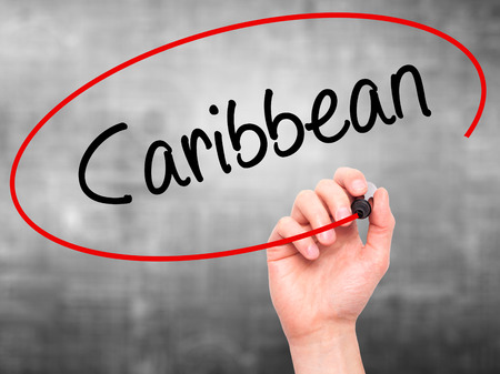 port au prince: Man Hand writing Caribbean with black marker on visual screen. Isolated on grey. Business, technology, internet concept. Stock Photo Stock Photo
