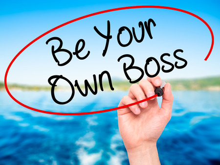 self starter: Man Hand writing Be Your Own Boss with black marker on visual screen. Isolated on nature. Business, technology, internet concept. Stock Image