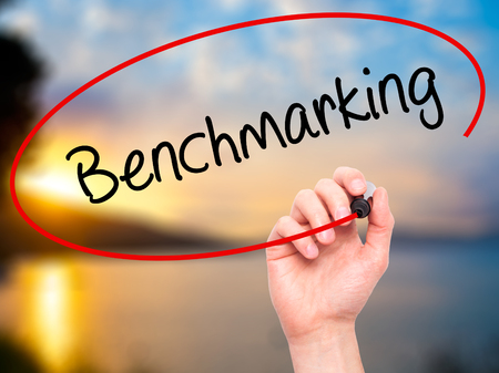 benchmarking: Man Hand writing Benchmarking  with black marker on visual screen. Isolated on nature. Business, technology, internet concept. Stock Photo Stock Photo