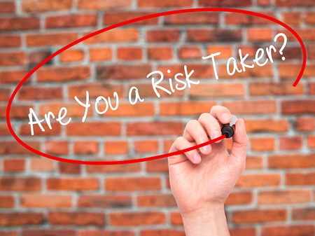 taker: Man Hand writing Are You a Risk Taker? with black marker on visual screen. Isolated on bricks. Business, technology, internet concept. Stock Photo
