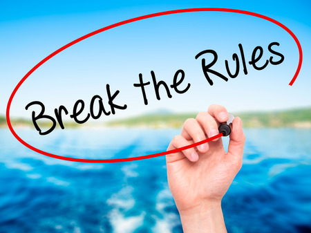libertarian: Man Hand writing Break the Rules with black marker on visual screen. Isolated on nature. Business, technology, internet concept. Stock Photo
