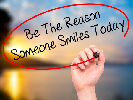 positiveness: Man Hand writing Be The Reason Someone Smiles Today  with black marker on visual screen. Isolated on nature. Business, technology, internet concept. Stock Photo