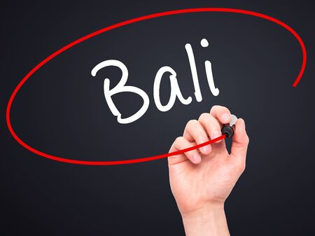 bali province: Man Hand writing Bali  with black marker on visual screen. Isolated on black. Business, technology, internet concept. Stock Photo