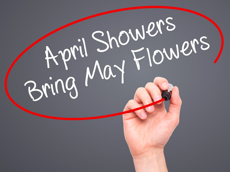 april showers: Man Hand writing April Showers Bring May Flowers with black marker on visual screen. Isolated on grey. Business, technology, internet concept. Stock Photo