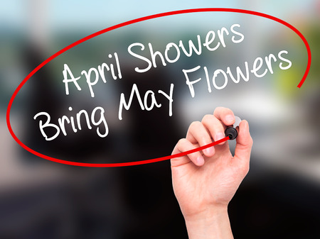 april flowers: Man Hand writing April Showers Bring May Flowers with black marker on visual screen. Isolated on office. Business, technology, internet concept. Stock Photo