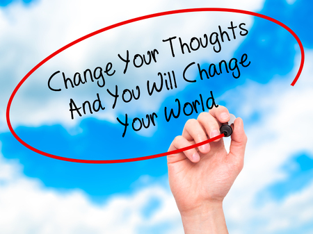 Man Hand writing Change Your Thoughts And You Will Change Your World with black marker on visual screen. Isolated on sky. Business, internet concept. Stock Photo