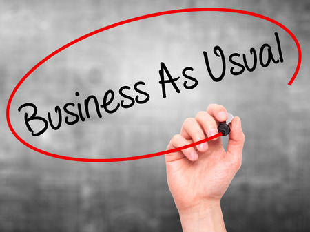 Man Hand writing Business As Usual with black marker on visual screen. Isolated on background. Business, technology, internet concept. Stock Photo Stock Photo