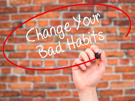 bad planning: Man Hand writing Change Your Bad Habits  with black marker on visual screen. Isolated on bricks. Business, technology, internet concept. Stock Photo