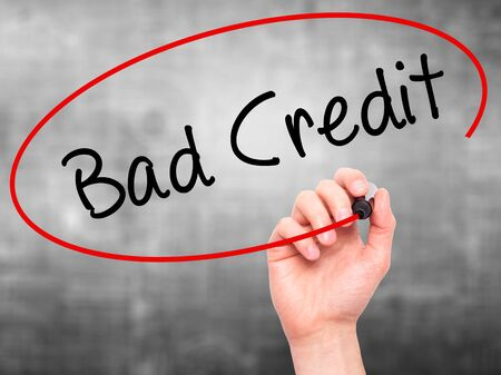 budget repair: Man Hand writing Bad Credit with black marker on visual screen. Isolated on grey. Business, technology, internet concept. Stock Photo