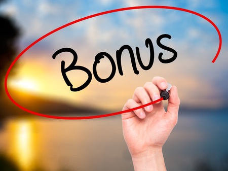 additional compensation: Man Hand writing Bonus with black marker on visual screen. Isolated on background. Business, technology, internet concept. Stock Photo
