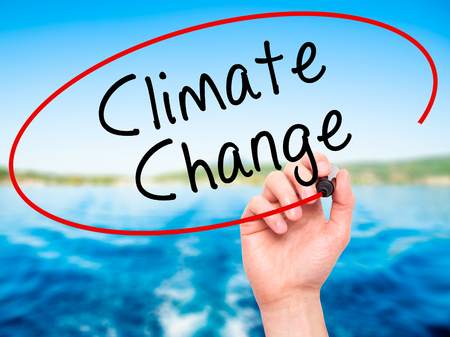 climate change: Man Hand writing Climate Change with black marker on visual screen. Isolated on nature. Business, technology, internet concept. Stock Photo