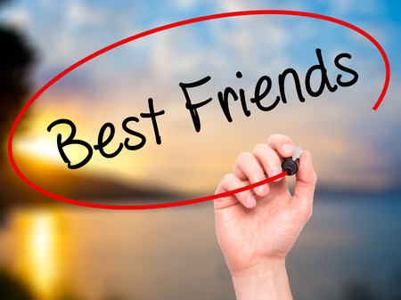 best schools: Man Hand writing Best Friends with black marker on visual screen. Isolated on nature. Business, technology, internet concept. Stock Photo