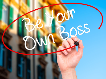 self starter: Man Hand writing Be Your Own Boss with black marker on visual screen. Isolated on city. Business, technology, internet concept. Stock Image