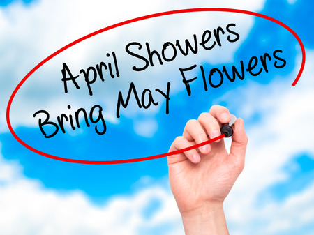 april flowers: Man Hand writing April Showers Bring May Flowers with black marker on visual screen. Isolated on sky. Business, technology, internet concept. Stock Photo