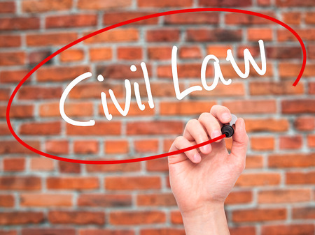 Man Hand writing Civil Law with black marker on visual screen. Isolated on bricks. Business, technology, internet concept.