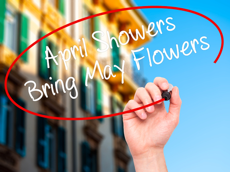 april flowers: Man Hand writing April Showers Bring May Flowers with black marker on visual screen. Isolated on city. Business, technology, internet concept. Stock Photo