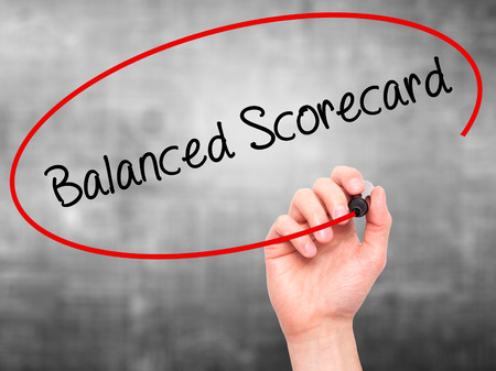 balanced budget: Man Hand writing Balanced Scorecard with black marker on visual screen. Isolated on grey. Business, technology, internet concept. Stock Photo
