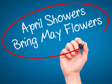 april: Man Hand writing April Showers Bring May Flowers with black marker on visual screen. Isolated on blue. Business, technology, internet concept. Stock Photo Stock Photo