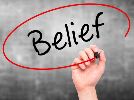 Man Hand writing Belief with black marker on visual screen. Isolated on grey. Business, technology, internet concept. Stock Photo