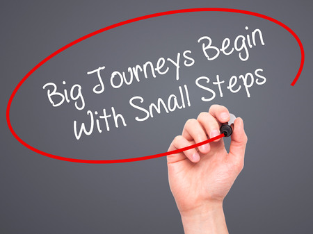 daunting: Man Hand writing Big Journeys Begin With Small Steps  with black marker on visual screen. Isolated on grey. Business, technology, internet concept. Stock Photo