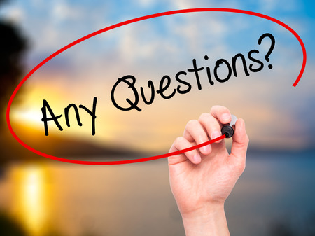 question marks: Man Hand writing Any Questions? with black marker on visual screen. Isolated on nature. Business, technology, internet concept. Stock Photo