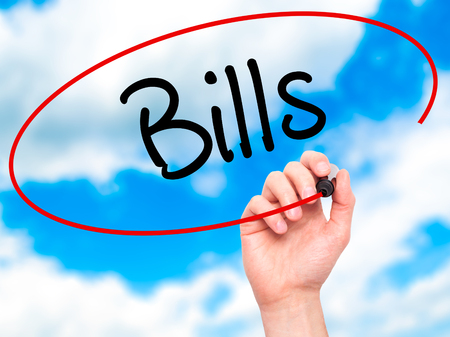 insolvent: Man Hand writing Bills with black marker on visual screen. Isolated on background. Business, technology, internet concept. Stock Photo
