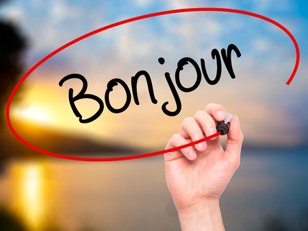 bonjour: Man Hand writing Bonjour  (Good Morning in French) with black marker on visual screen. Isolated on background. Business, technology, internet concept. Stock Photo