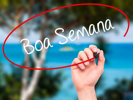 semana: Man Hand writing Boa semana   (Good WeekIn portuguese)with black marker on visual screen. Isolated on nature. Business, technology, internet concept. Stock Photo
