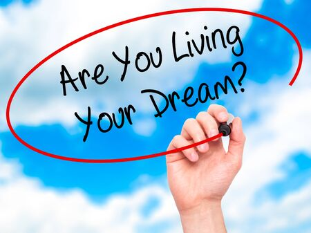 jargon: Man Hand writing Are You Living Your Dream? with black marker on visual screen. Isolated on sky. Business, technology, internet concept. Stock Photo