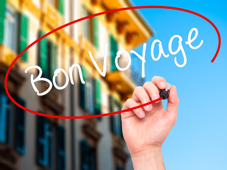farewell: Man Hand writing  Bon Voyage  (Have a Good Trip In French)  with black marker on visual screen. Isolated on background. Business, technology, internet concept. Stock Photo