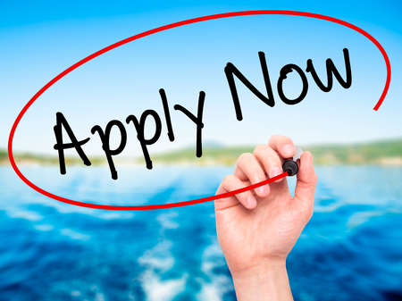 e recruitment: Man Hand writing Apply Now with black marker on visual screen. Isolated on nature. Business, technology, internet concept. Stock Photo