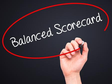 balanced budget: Man Hand writing Balanced Scorecard with black marker on visual screen. Isolated on black. Business, technology, internet concept. Stock Photo