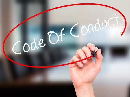 work ethic responsibilities: Man Hand writing Code Of Conduct with black marker on visual screen. Isolated on office. Business, technology, internet concept. Stock Photo