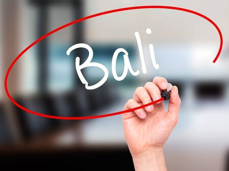 bali province: Man Hand writing Bali  with black marker on visual screen. Isolated on office. Business, technology, internet concept. Stock Photo Stock Photo