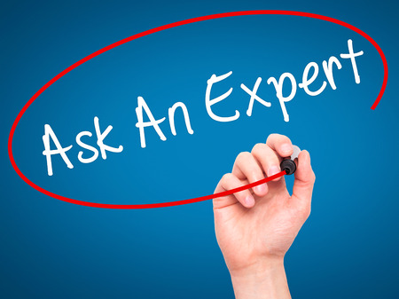 warranty questions: Man Hand writing Ask An Expert with black marker on visual screen. Isolated on blue. Business, technology, internet concept. Stock Photo