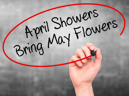 april: Man Hand writing April Showers Bring May Flowers with black marker on visual screen. Isolated on grey. Business, technology, internet concept. Stock Photo