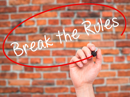 rebelling: Man Hand writing Break the Rules with black marker on visual screen. Isolated on bricks. Business, technology, internet concept. Stock Photo