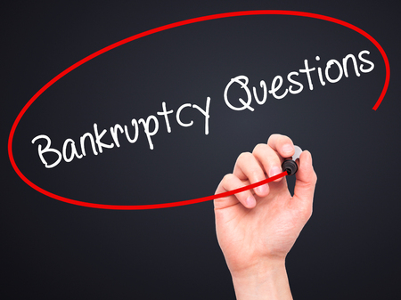 portable failure: Man Hand writing Bankruptcy Questions with black marker on visual screen. Isolated on black. Business, technology, internet concept. Stock Photo