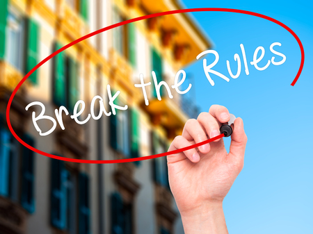 rebelling: Man Hand writing Break the Rules with black marker on visual screen. Isolated on city. Business, technology, internet concept. Stock Photo Stock Photo