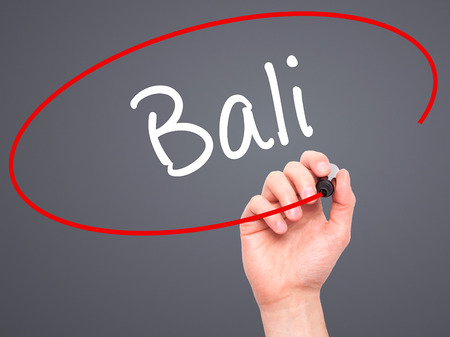 bali province: Man Hand writing Bali  with black marker on visual screen. Isolated on grey. Business, technology, internet concept. Stock Photo Stock Photo