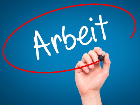 arbeit: Man Hand writing Arbeit (Work in German) with black marker on visual screen. Isolated on blue. Business, technology, internet concept. Stock Photo