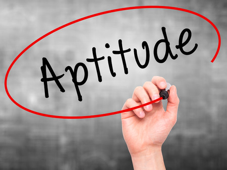 aptitude: Man Hand writing Aptitude with black marker on visual screen. Isolated on background. Business, technology, internet concept. Stock Photo