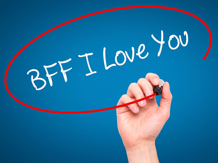 bff: Man Hand writing BFF I Love You with black marker on visual screen. Isolated on blue. Business, technology, internet concept.