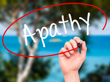 apathy: Man Hand writing Apathy  with black marker on visual screen. Isolated on background. Business, technology, internet concept. Stock Photo